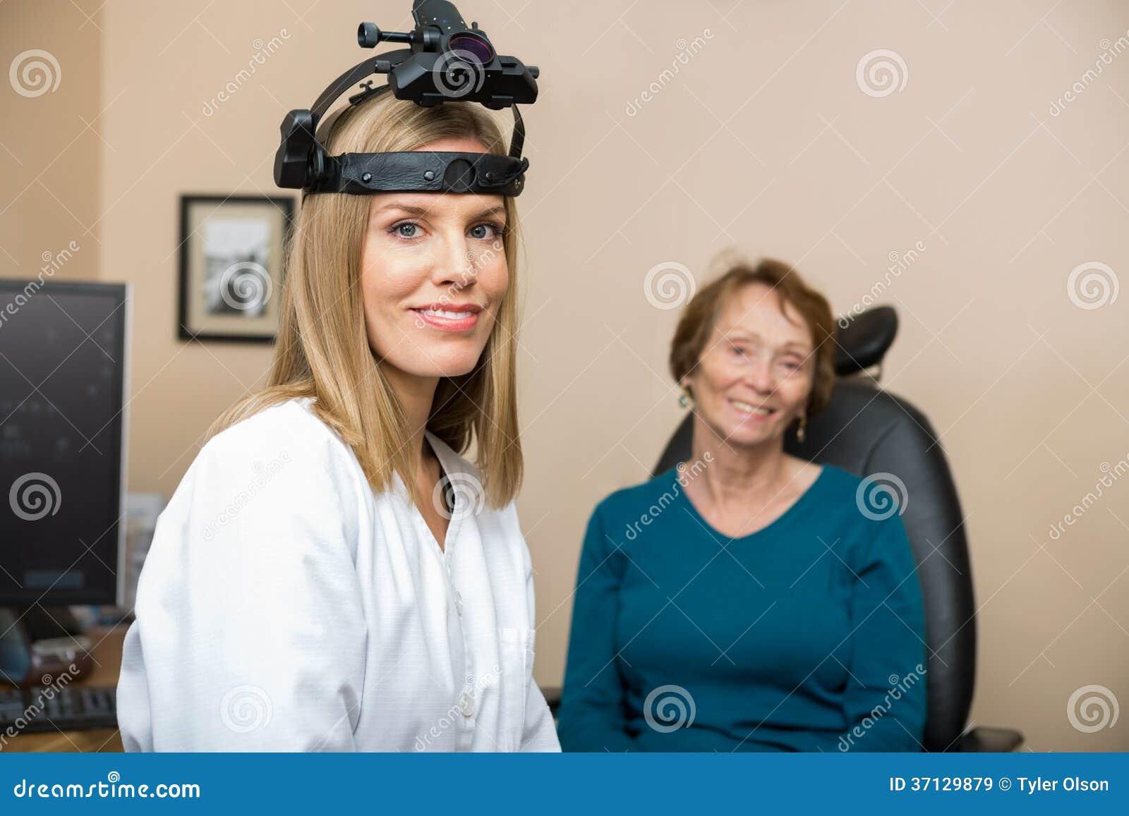 Confident Female Optometrist With Senior Patient Stock Image