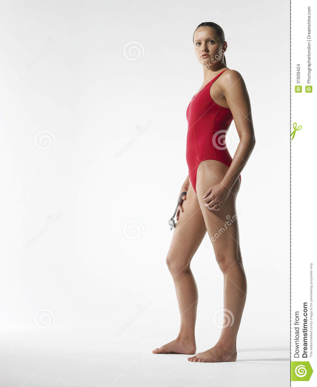 7709df45f330f Full length side view of a young female swimmer standing against white  background