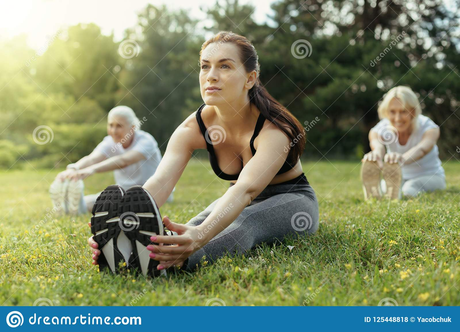 Confident female trainer stretching back during exercise