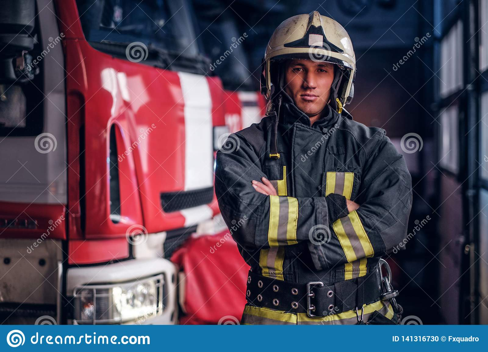 A confident fireman wearing protective uniform standing next to a fire engine in a garage of a fire department, crossed