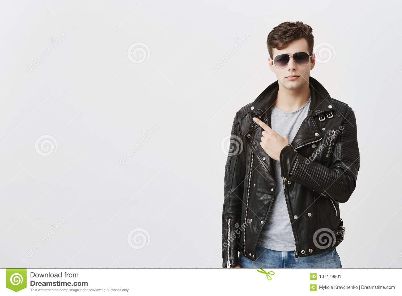 ea7b746f153 Confident good-looking guy dressed in black leather jacket with sunglasses  on