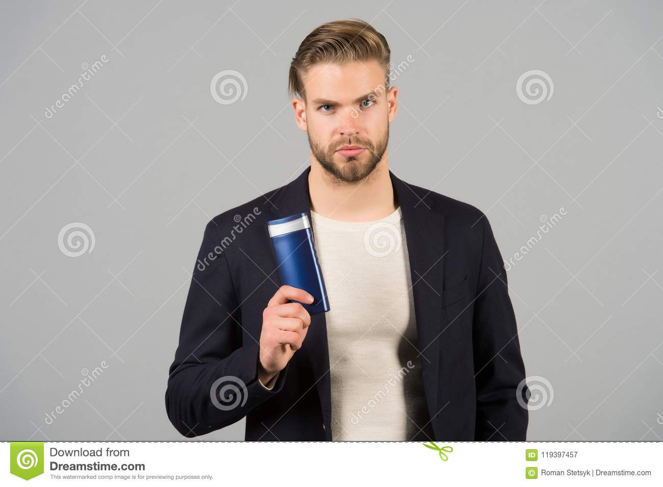 Confident in hair care product. Man stylish hairstyle holds bottle hygienic product grey background. Switch matte