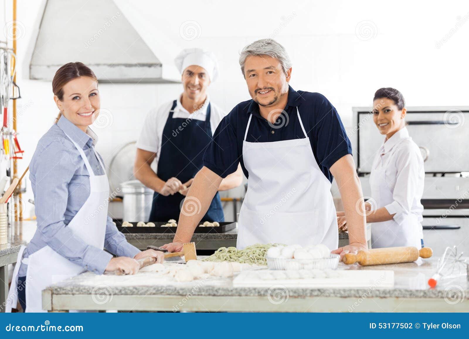 Confident Male And Female Chefs Preparing Pasta At