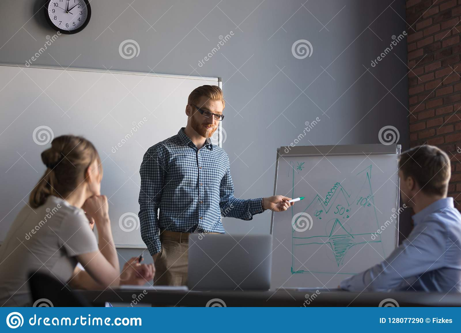 Confident male leader or business coach giving presentation to c