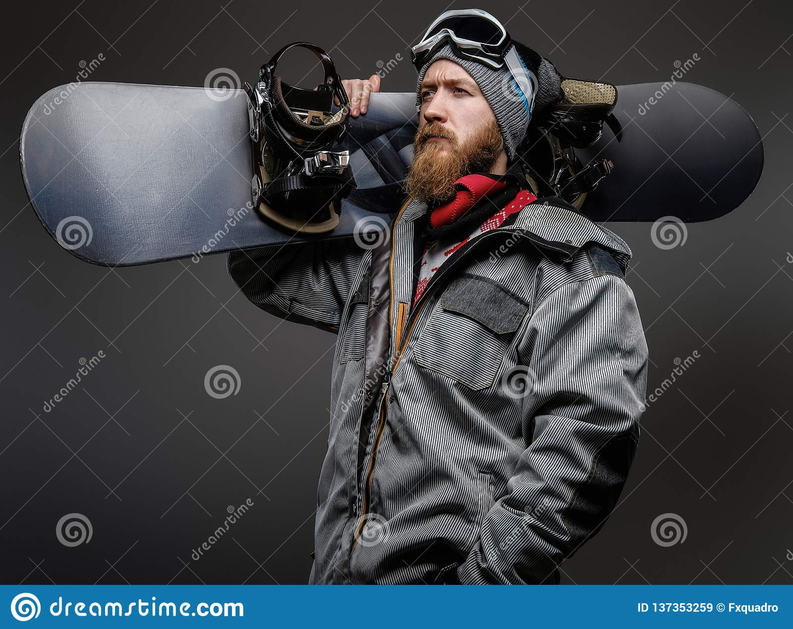 Confident man with a red beard wearing a full equipment holding a snowboard on his shoulder, looking away with a serious