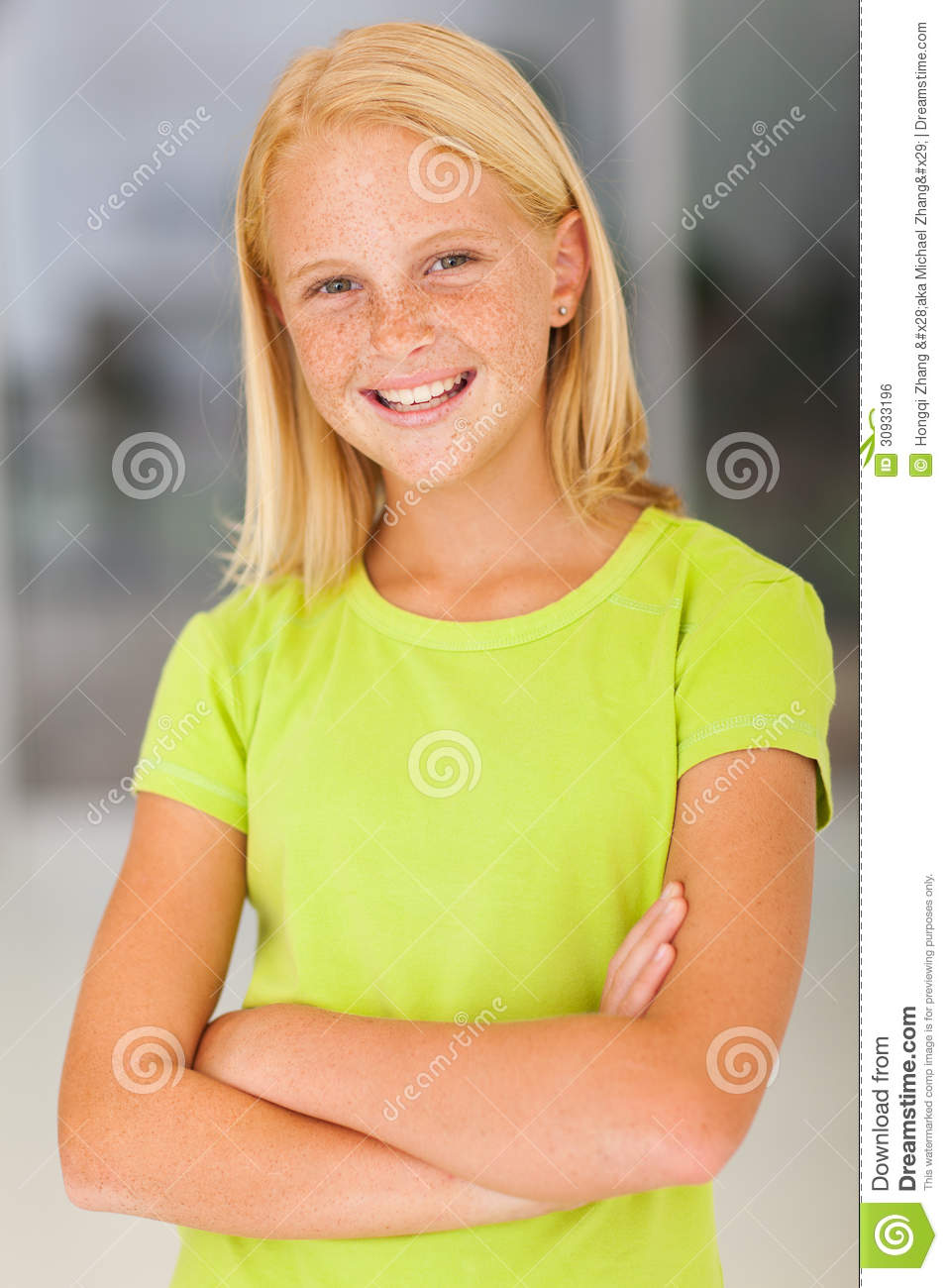 Confident preteen girl portrait with arms crossed.