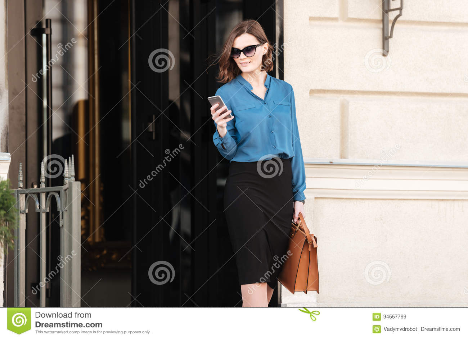 Confident pretty woman in sunglasses using mobile phone