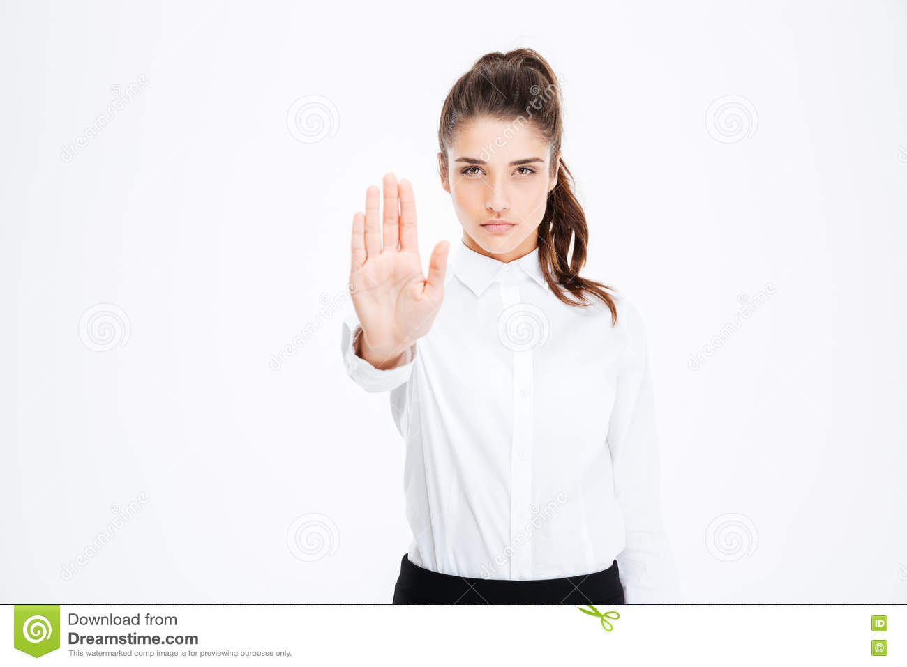 Confident pretty young businesswoman standing and showing stop gesture