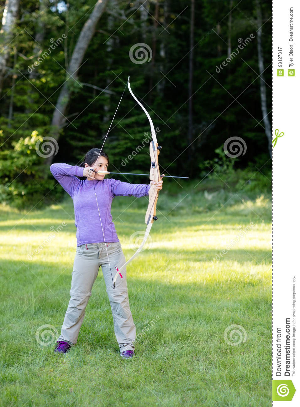 Confident Woman Aiming With Bow And Arrow In Forest Stock