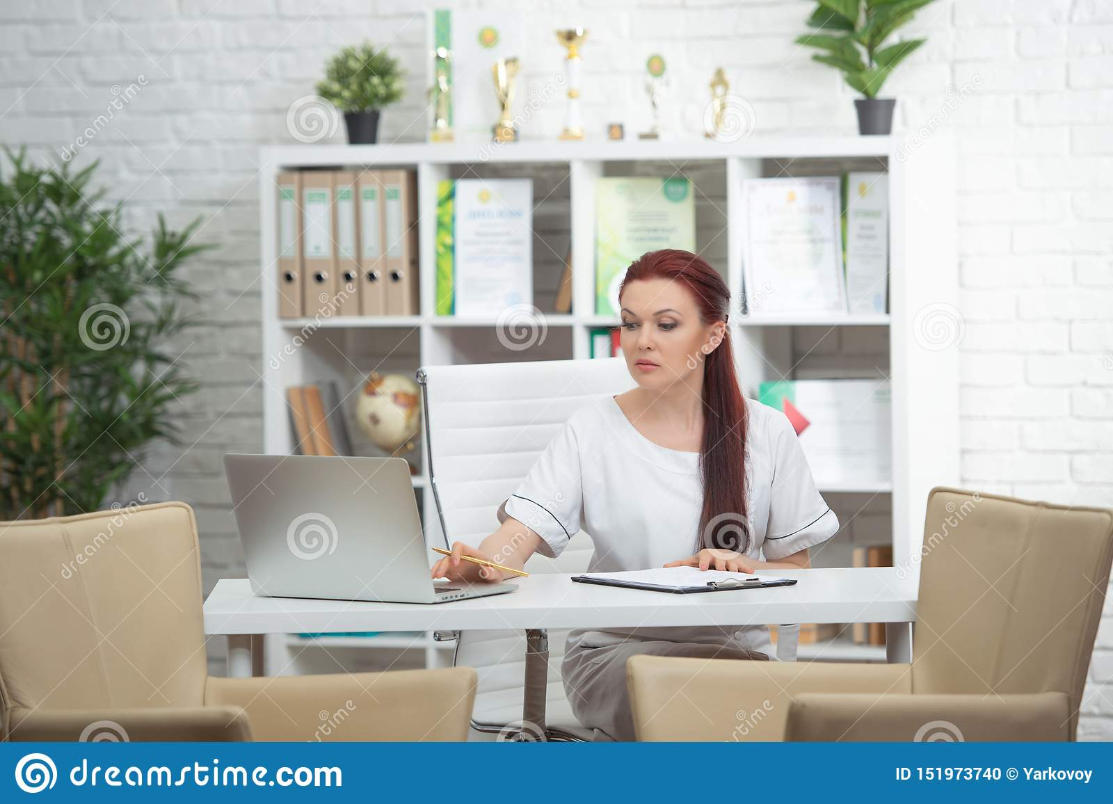 Confident woman doctor sitting at the table in her office and smiling at camera. healthcare concept