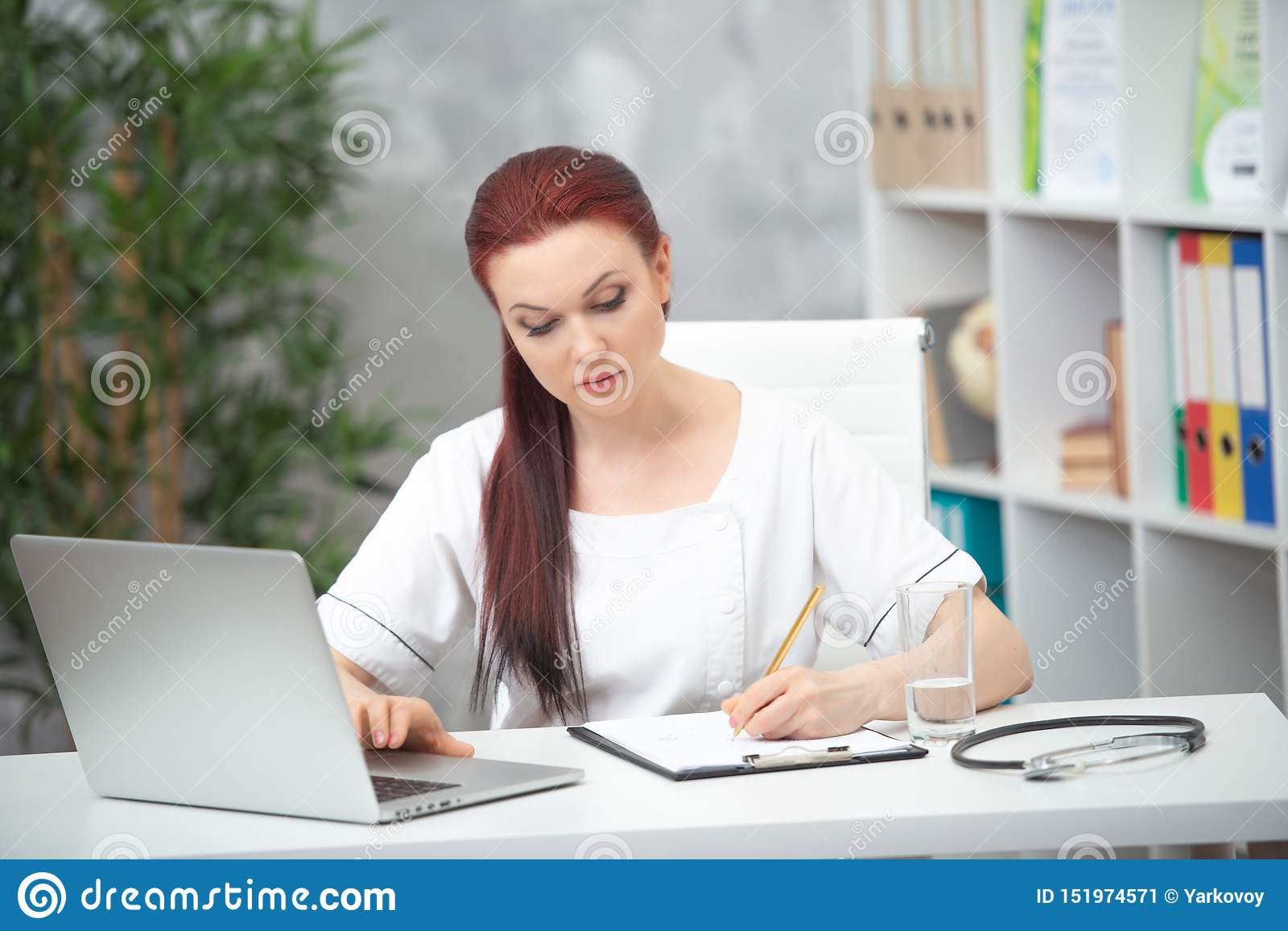 Confident woman doctor sitting at the table in her office and works at the computer. healthcare concept