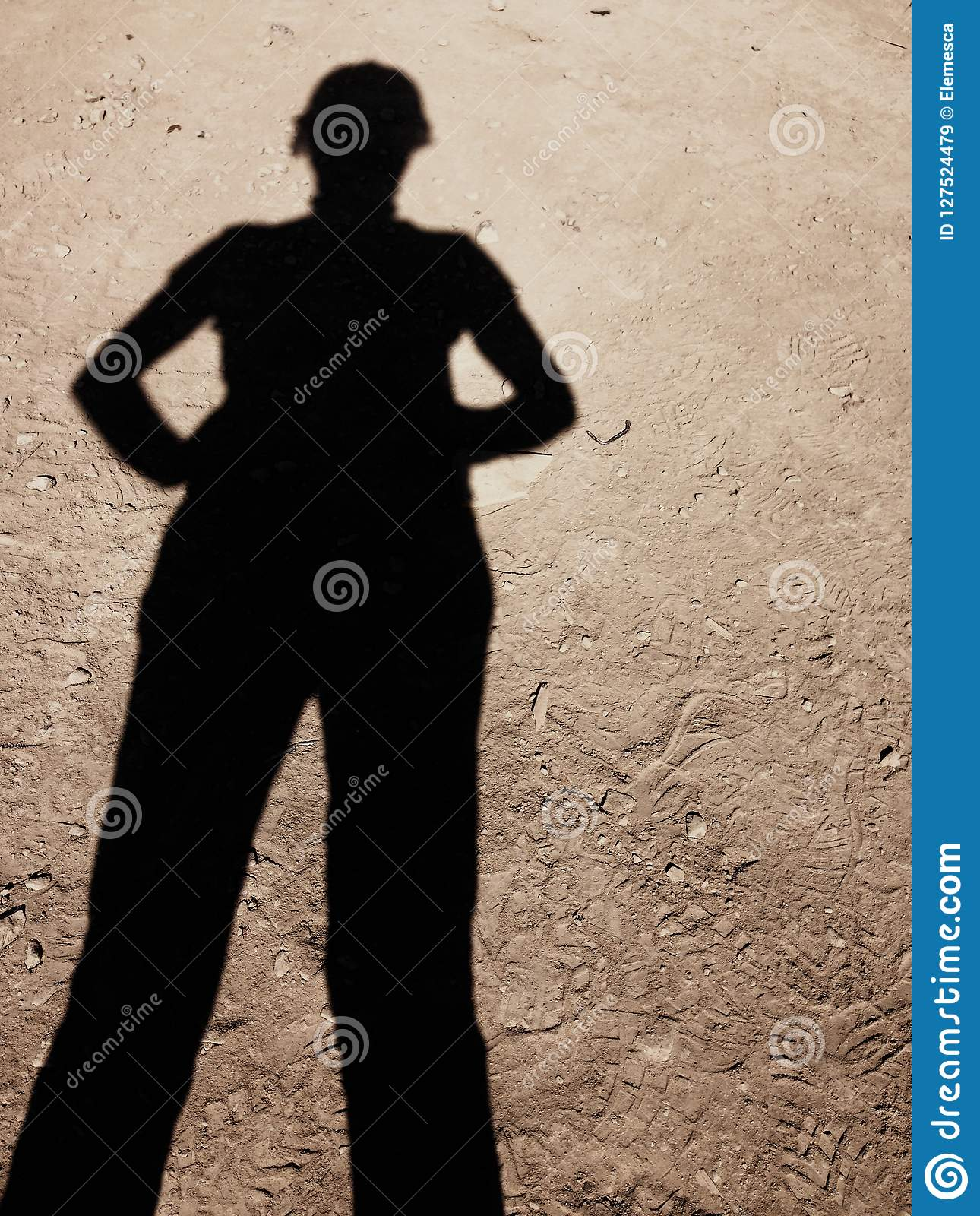 Confident woman`s shadow on construction ground