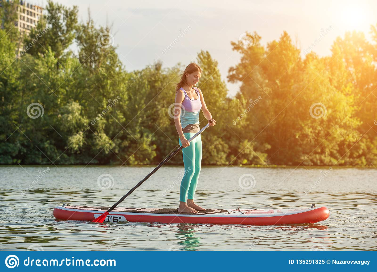 Confident woman standing with a paddle on the surfboard, SUP