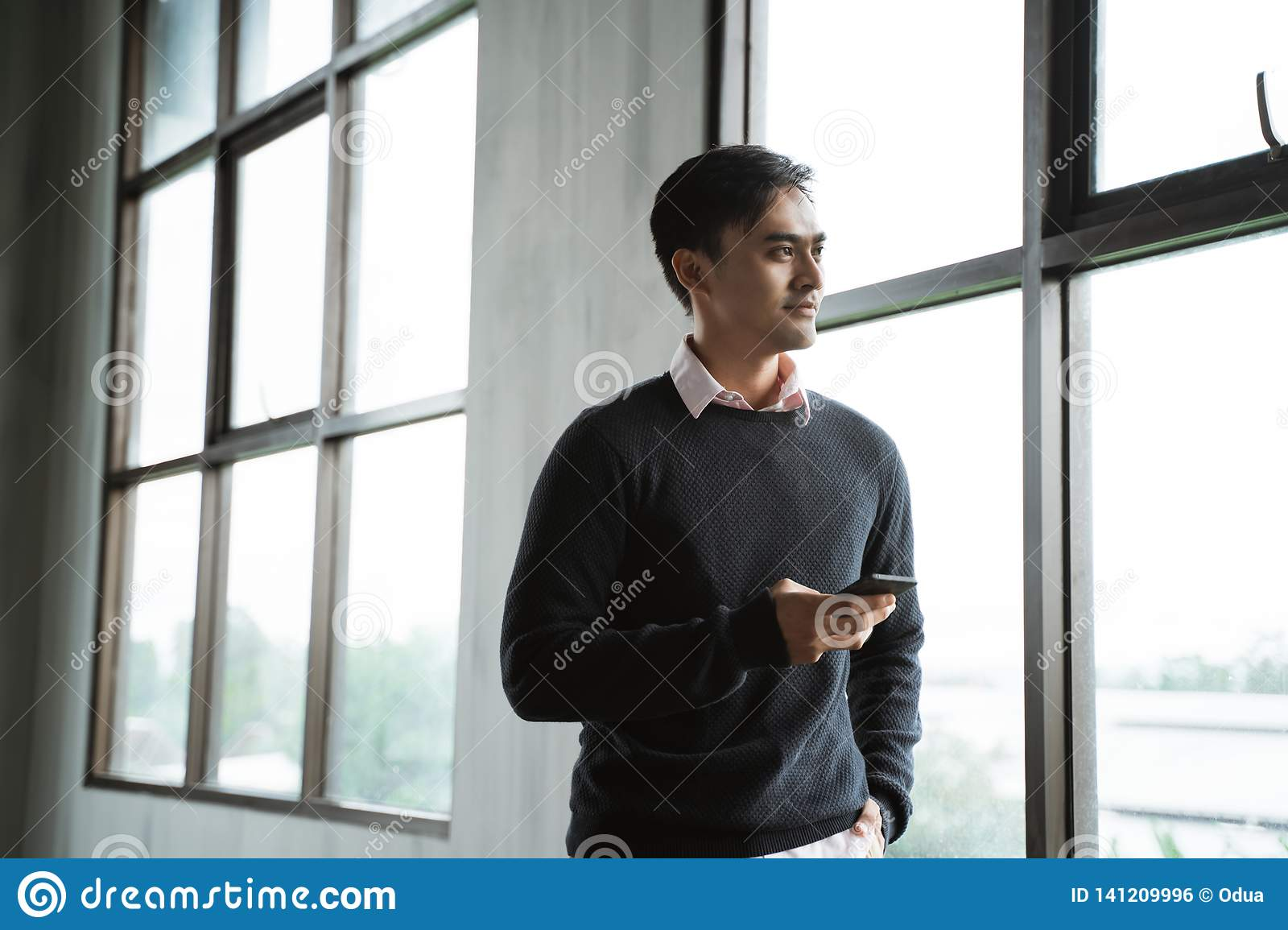 Confident young businessman using cell phone