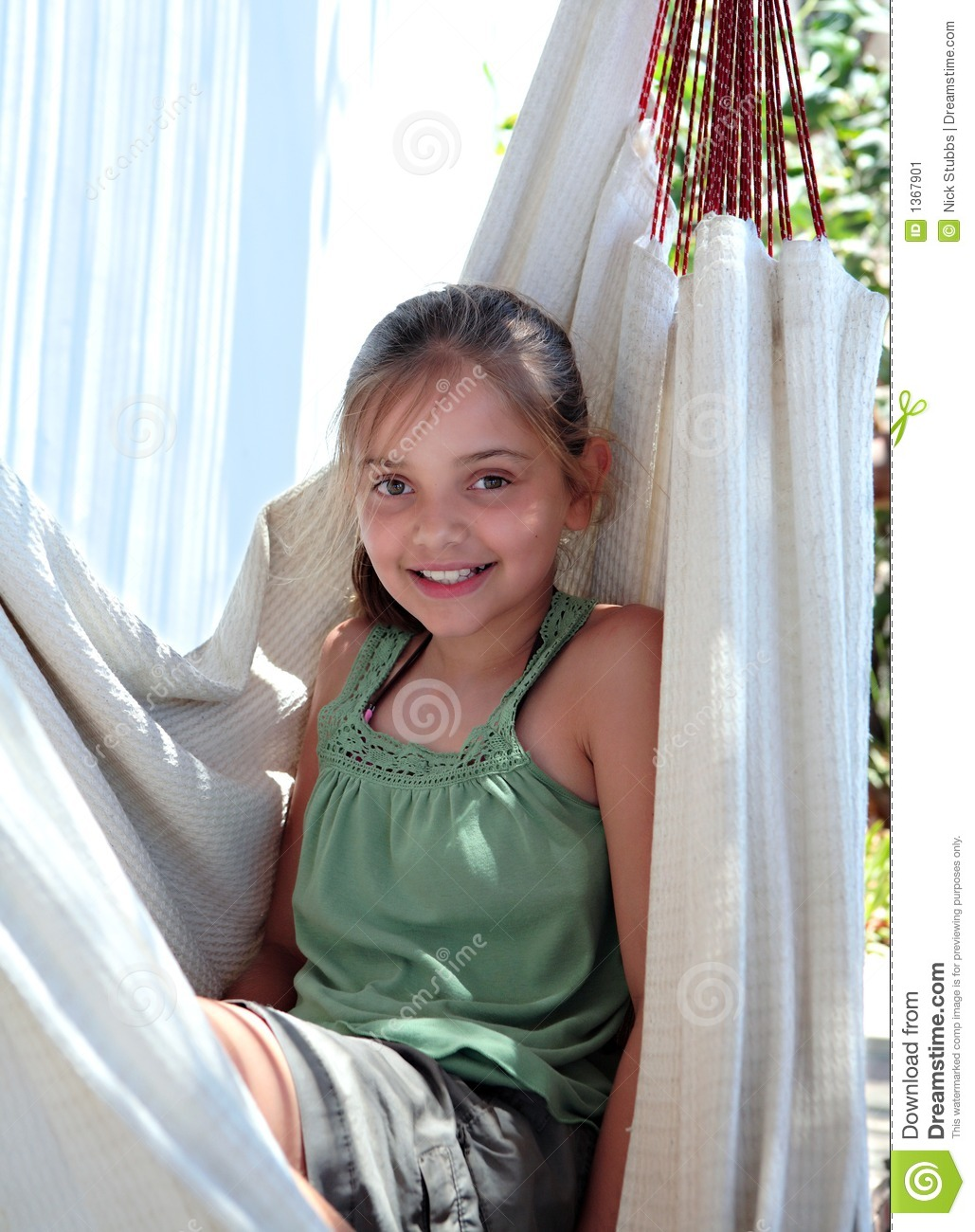 Confident Young Girl Sitting In Hammock On Vacation Stock ...