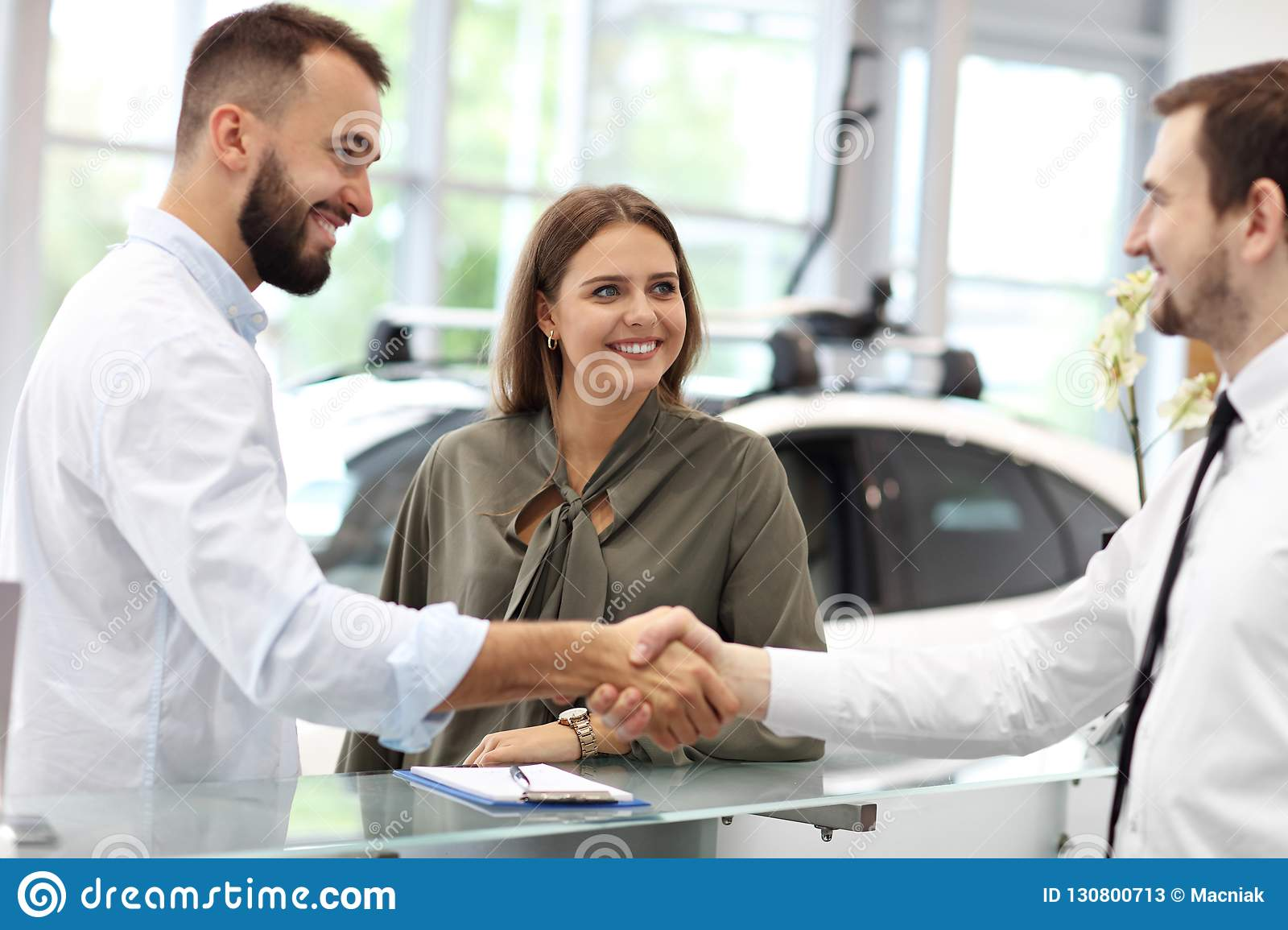 Confident young salesman explaining car features to the young attractive owners