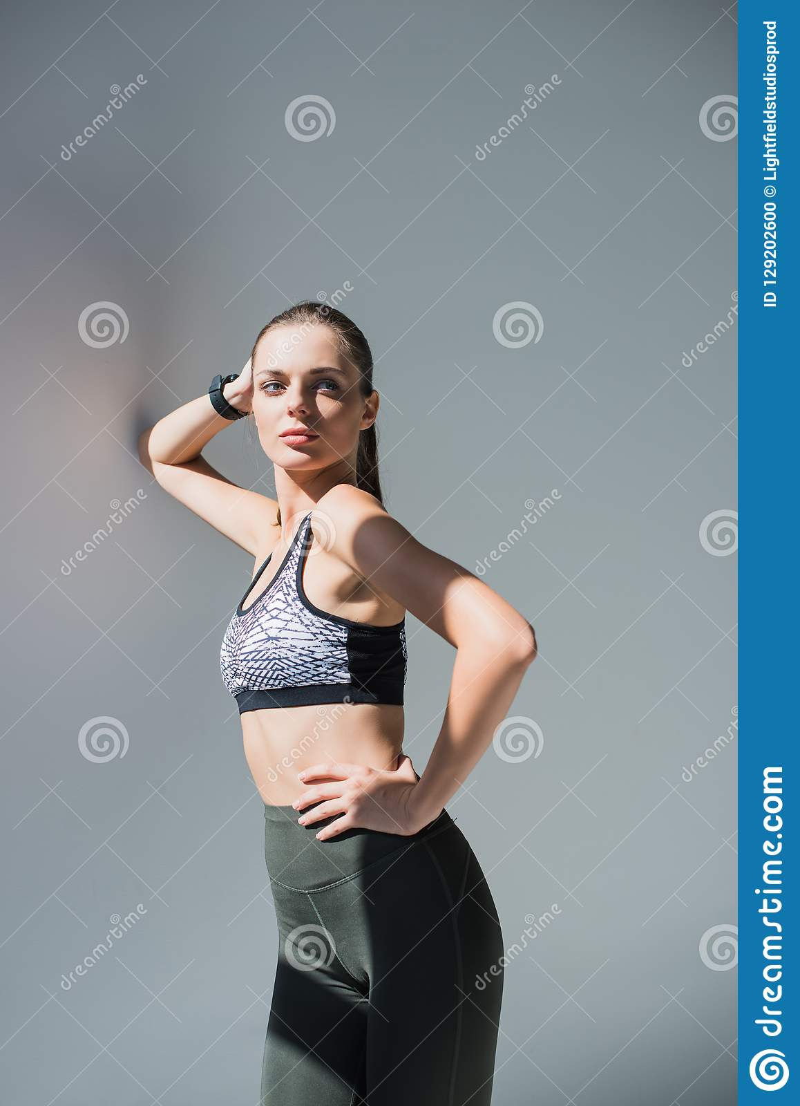 confident young sportswoman standing with hand on waist and looking away