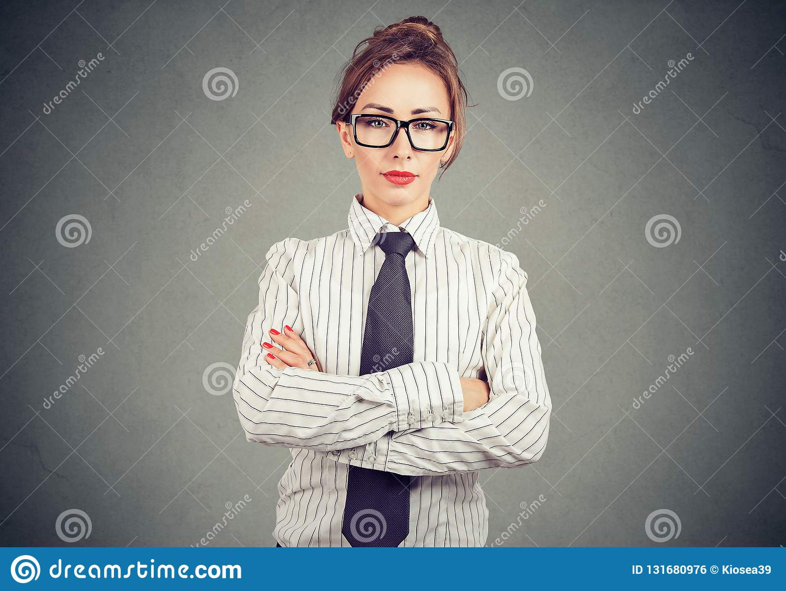 Confident woman in formal outfit and eyeglasses holding arms crossed and looking at camera