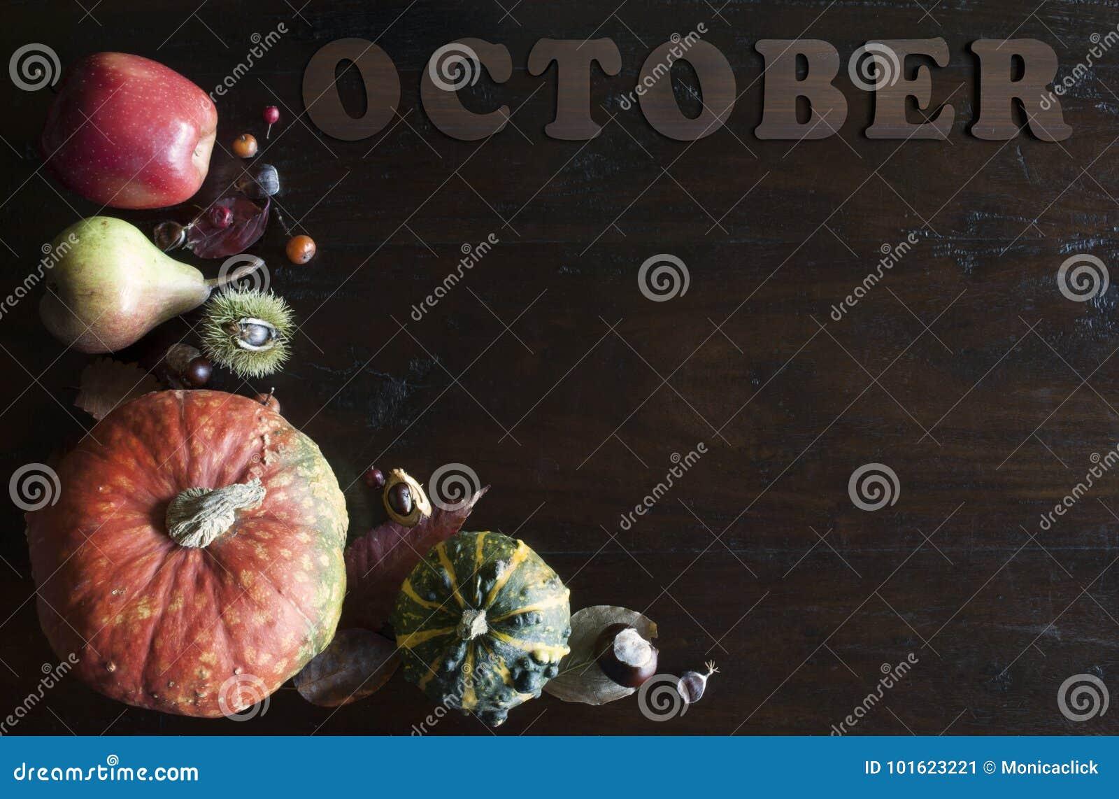 Configuração lisa da queda rústica bonita com folhas, abóboras, castanhas e letras outubro no fundo de madeira