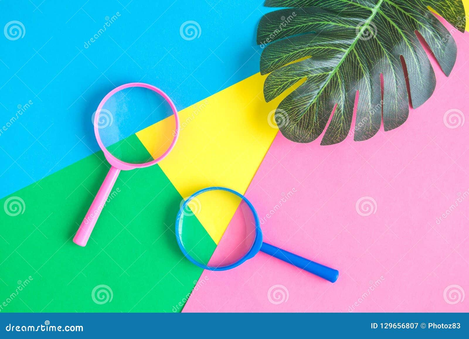 Configuração lisa das lentes de aumento com sumário verde das folhas no fundo colorido