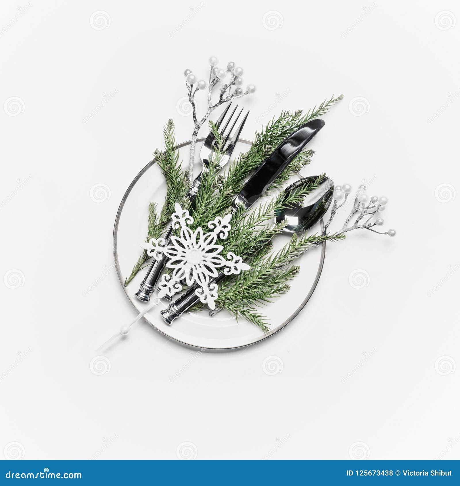 Configuration de table de Noël Plat avec des branches de sapin, des couverts et la décoration de fête de vacances : brindilles et