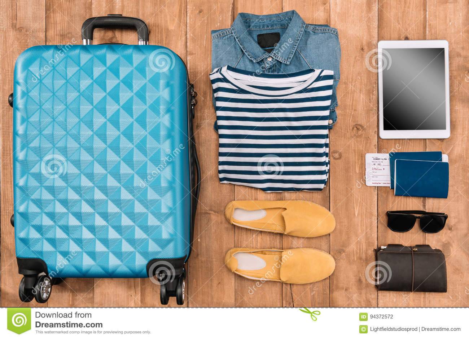 Configuration plate avec le bagage, les vêtements masculins, les accessoires et le comprimé numérique sur le plancher en bois