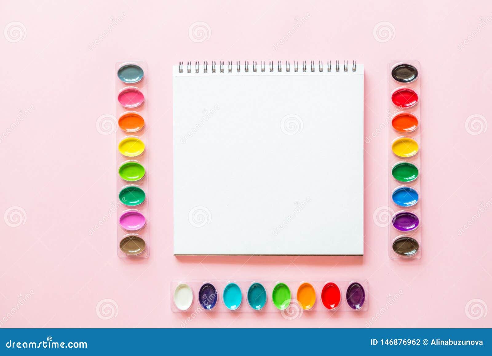 Configuration plate cr?ative des palettes et du carnet d aquarelle Lieu de travail d artiste sur un fond en pastel rose