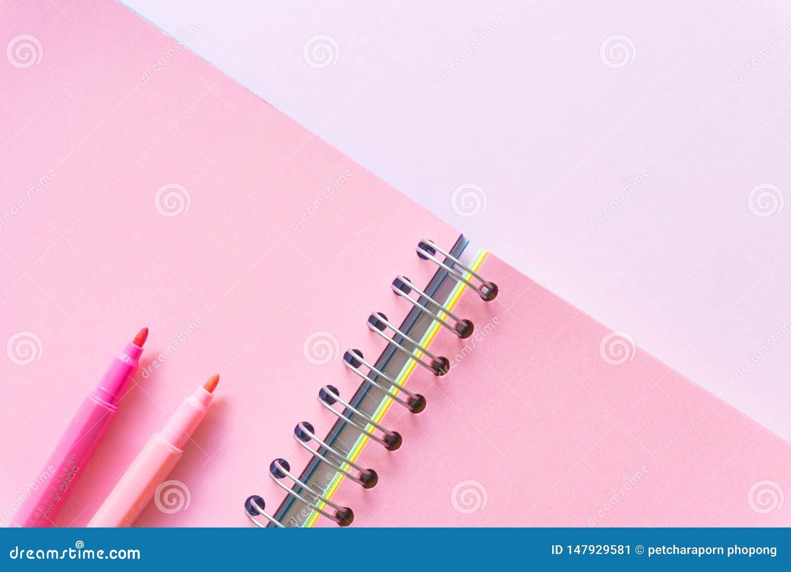 Configuration plate de carnet sur le fond rose en pastel de couleur, style minimal Espace de travail