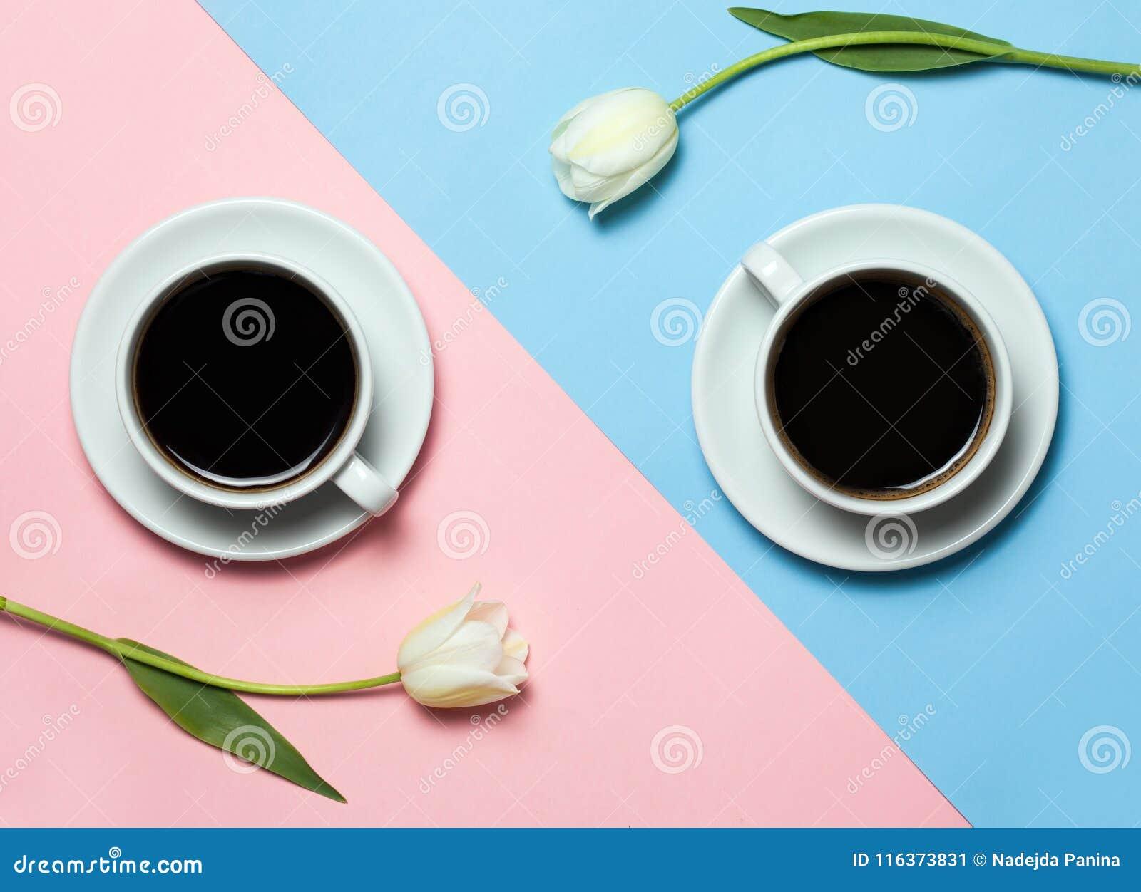 Configuration plate de la photo minimalistic de deux tasses de café et de tulipes sur le fond rose et jaune Concept de café de mi
