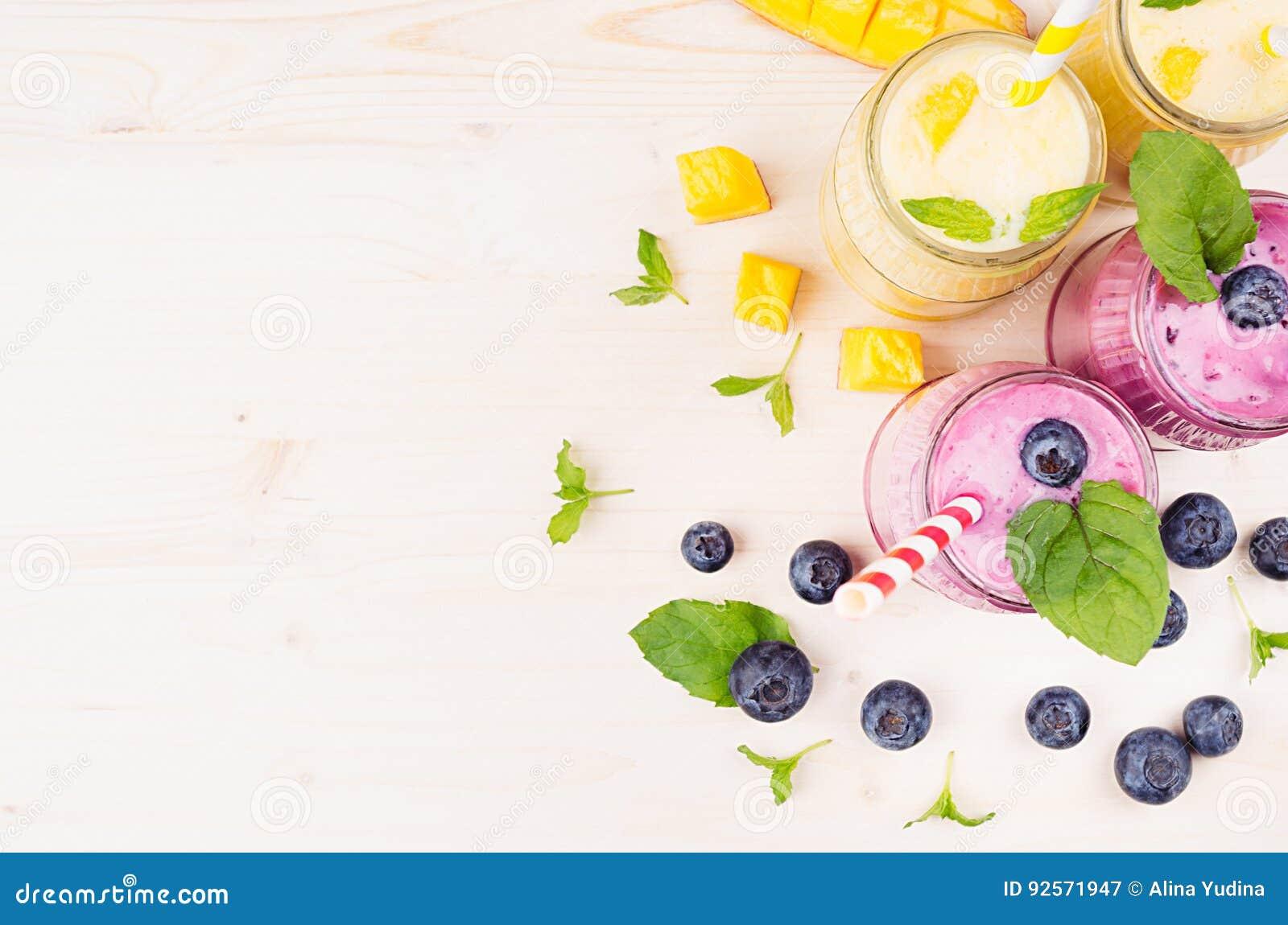 Confine decorativo del frullato giallo e viola della frutta in barattoli di vetro con paglia, foglie di menta, fette del mango, b