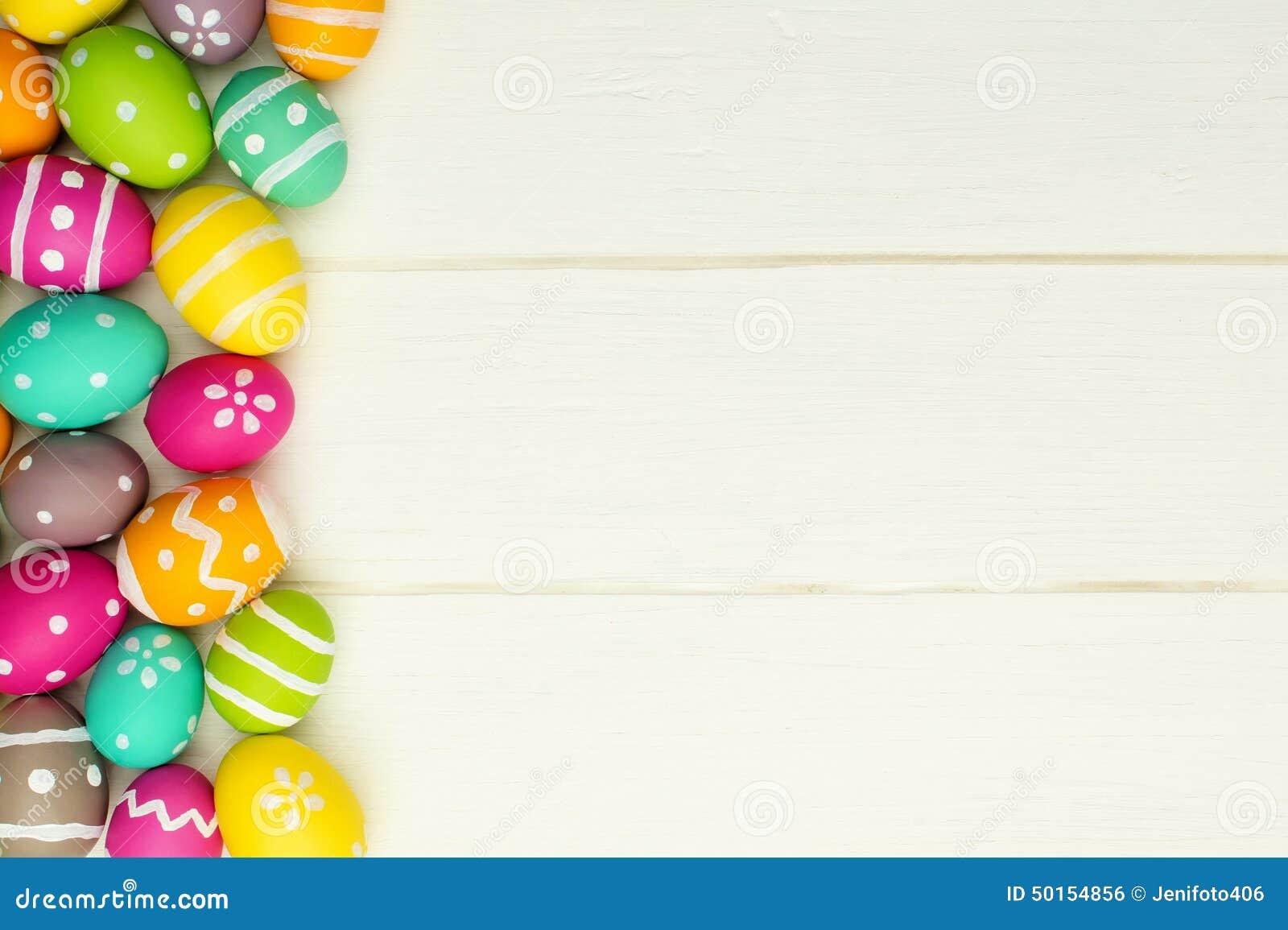 Confine del lato dell uovo di Pasqua contro legno bianco