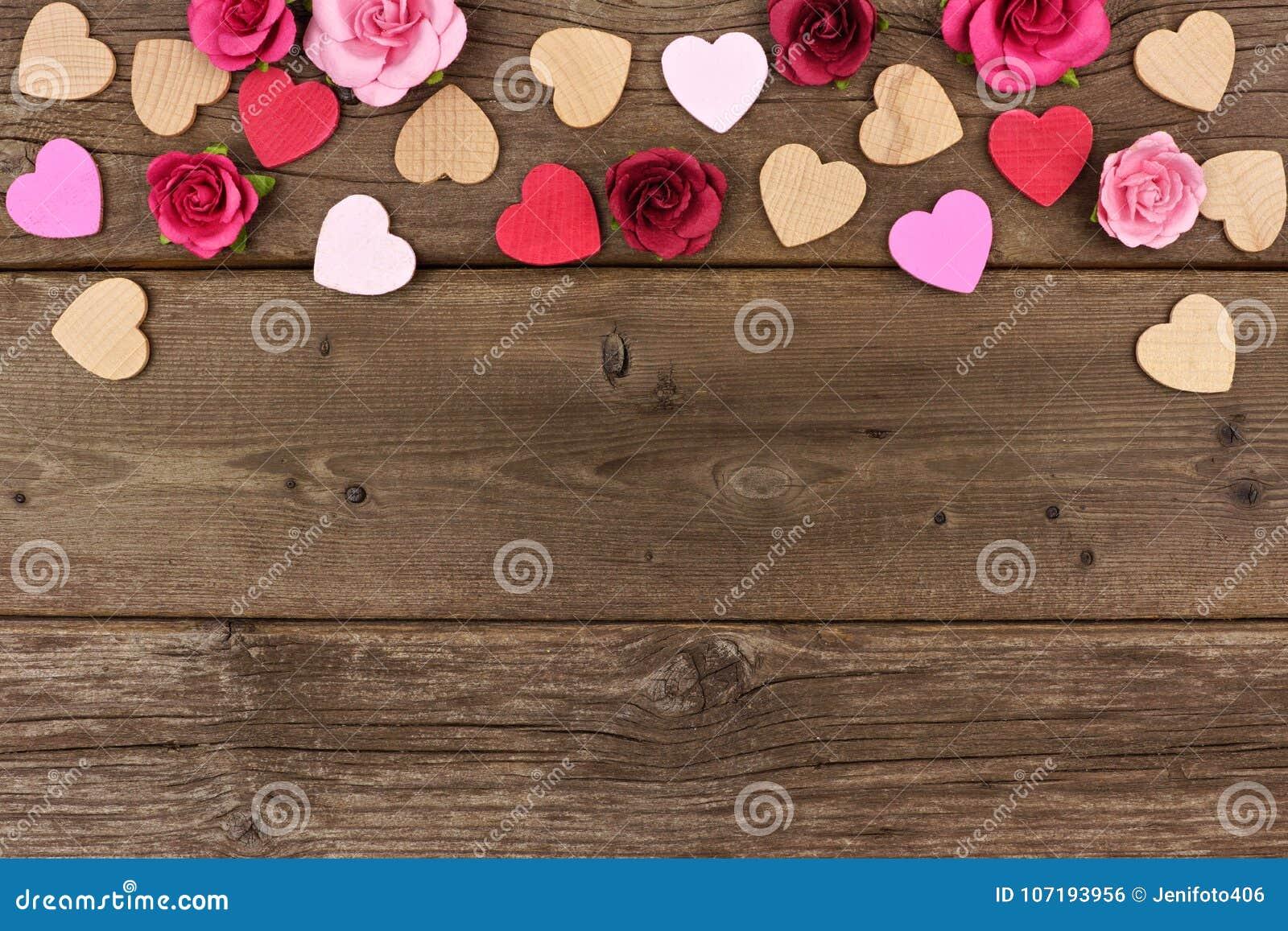 Confine della cima di giorno di biglietti di S. Valentino dei cuori e delle rose contro legno rustico