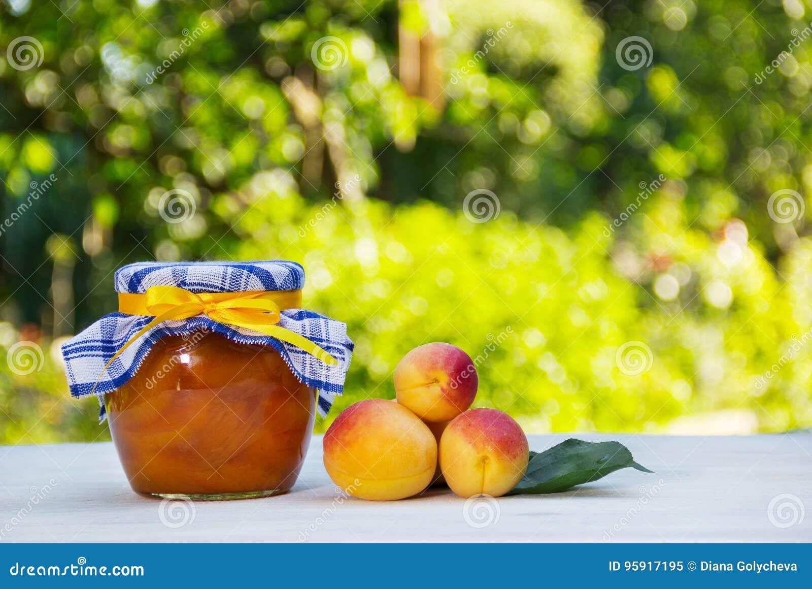 Confiture faite maison sur un fond naturel vert Un pot de confiture à la maison d abricot et d abricots frais sur une table blanc