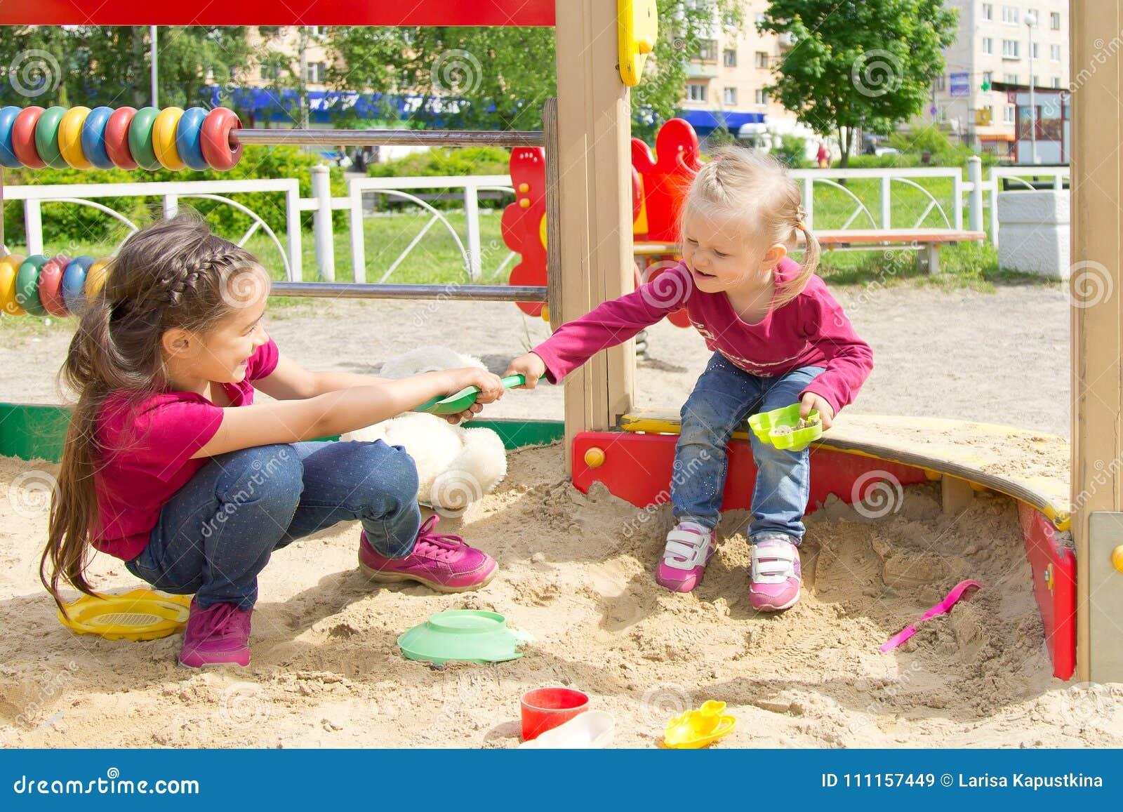Conflicto en el patio Dos niños que luchan sobre un juguete traspalan en la salvadera