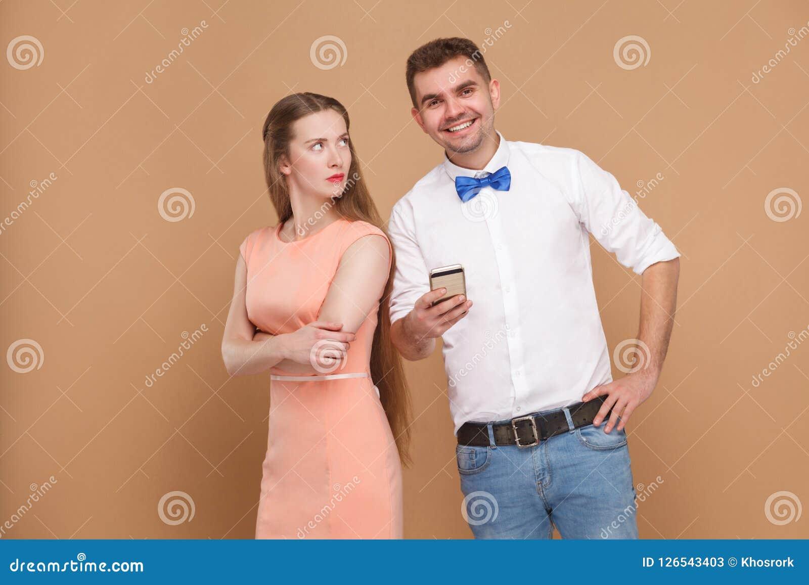 Conflicto Situación feliz del hombre, teléfono móvil de la tenencia y a de la mirada