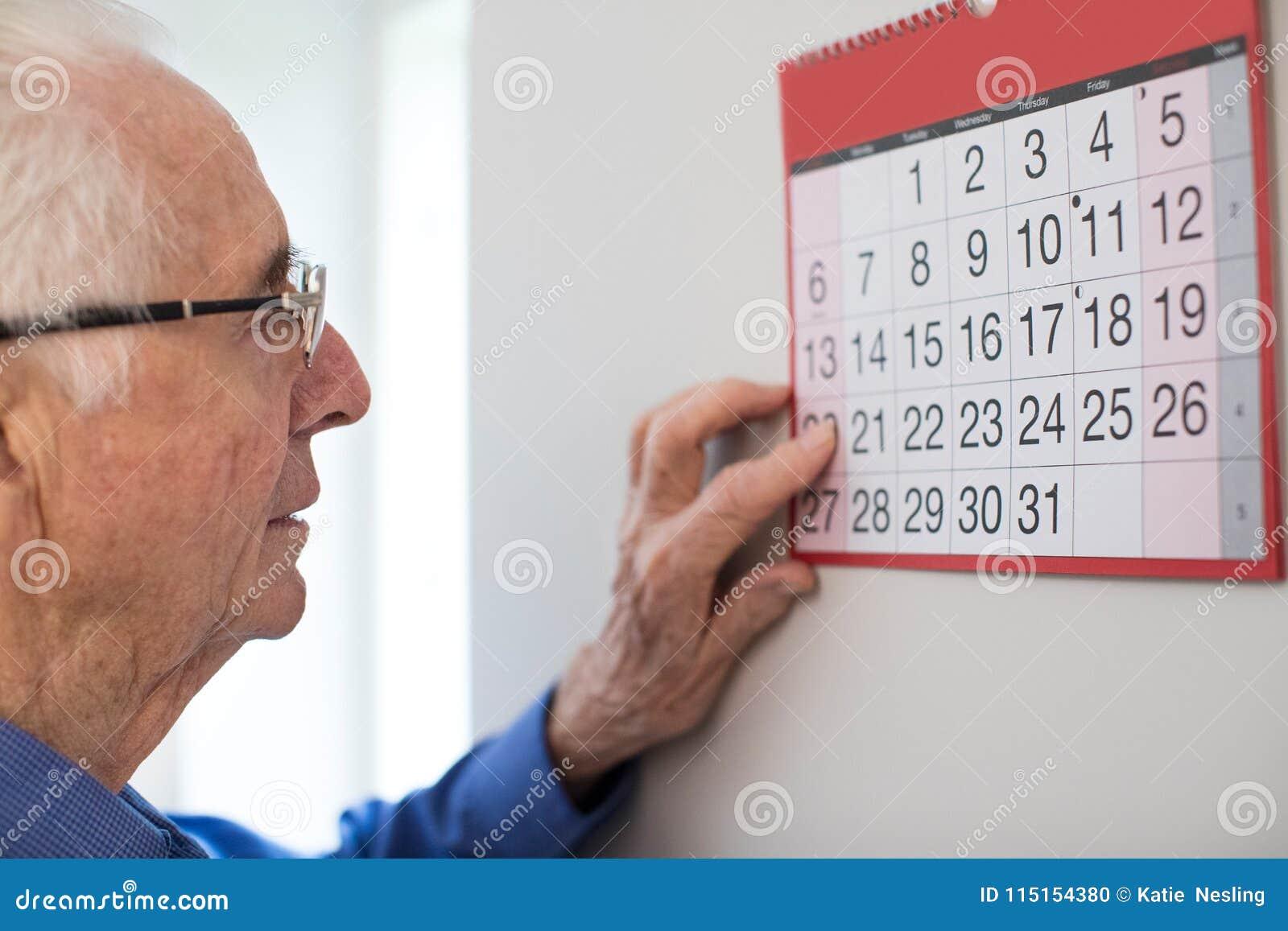 Confused старший человек при слабоумие смотря календарь стены