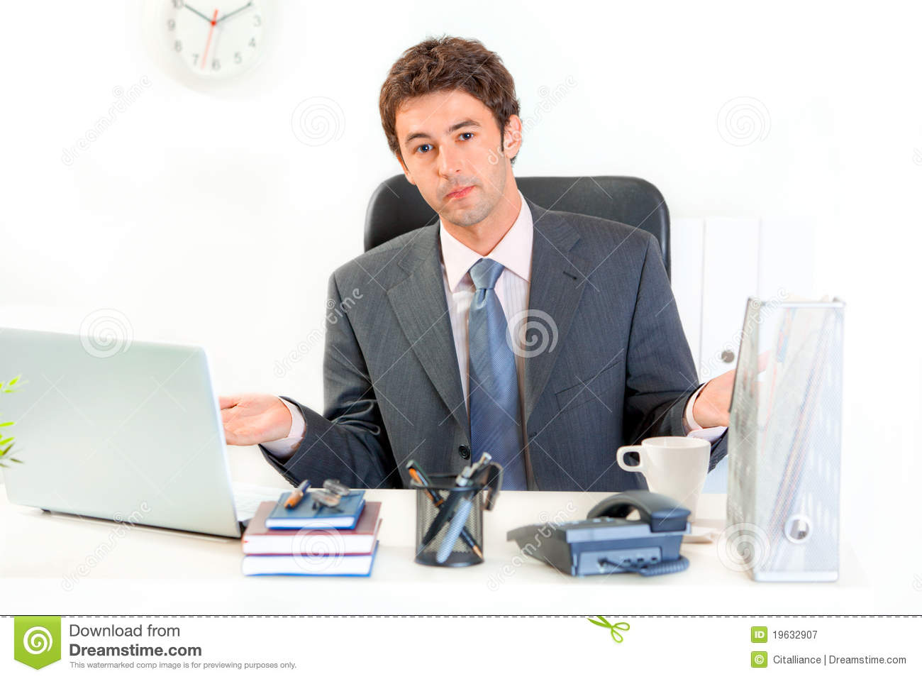 Confused Business Man Sitting At Office Desk Royalty Free