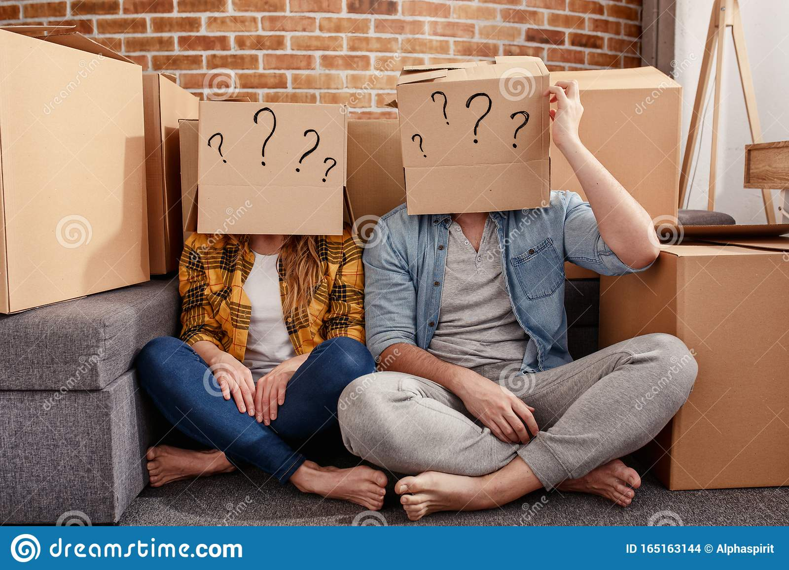 Confused couple of having to move and arrange all the packages. Concept of success, delusion, change , future, confusion