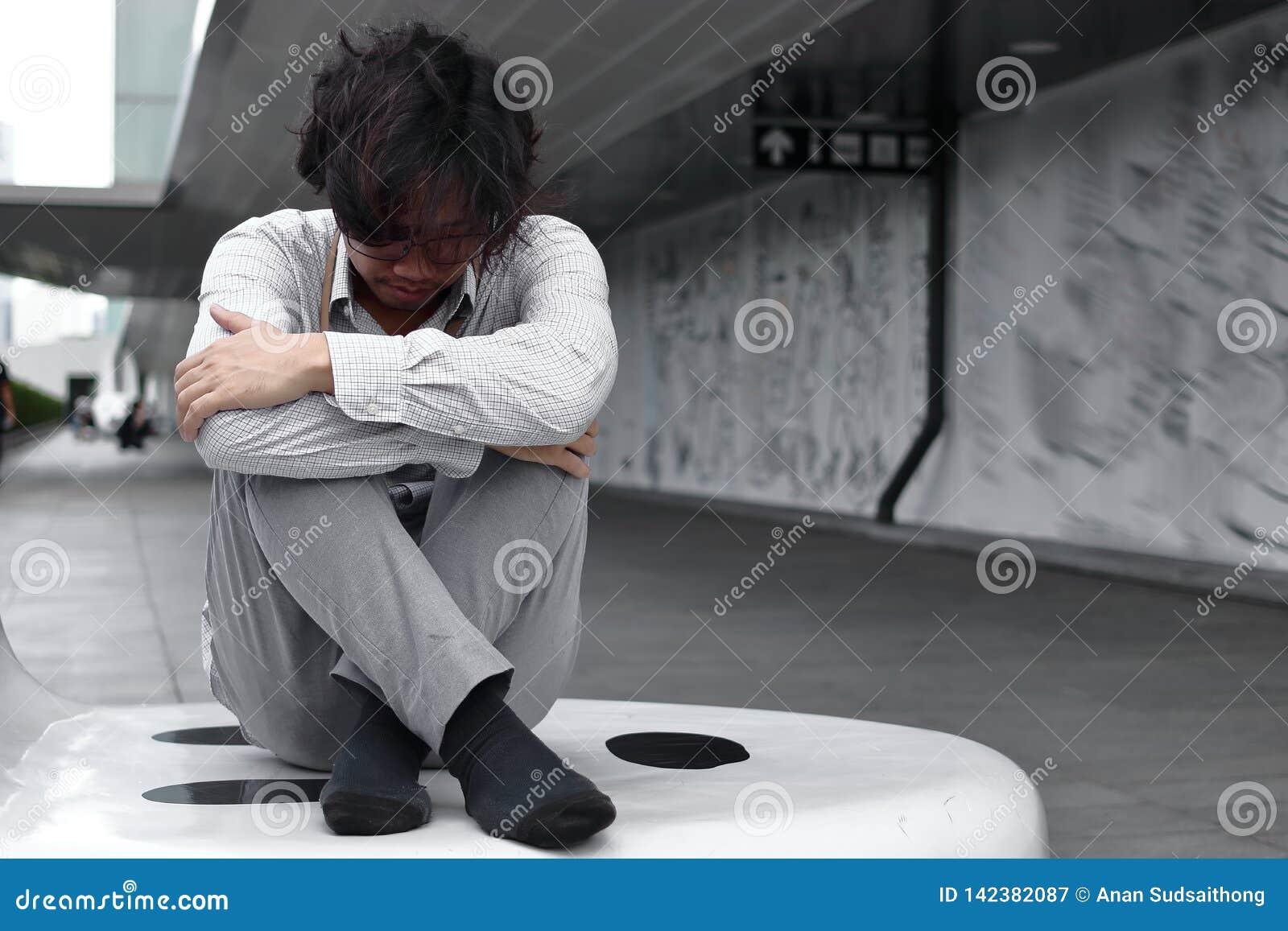 Confused sitter kramar den utmattade unga asiatiska affärsmannen och hans knä upp till bröstkorgen