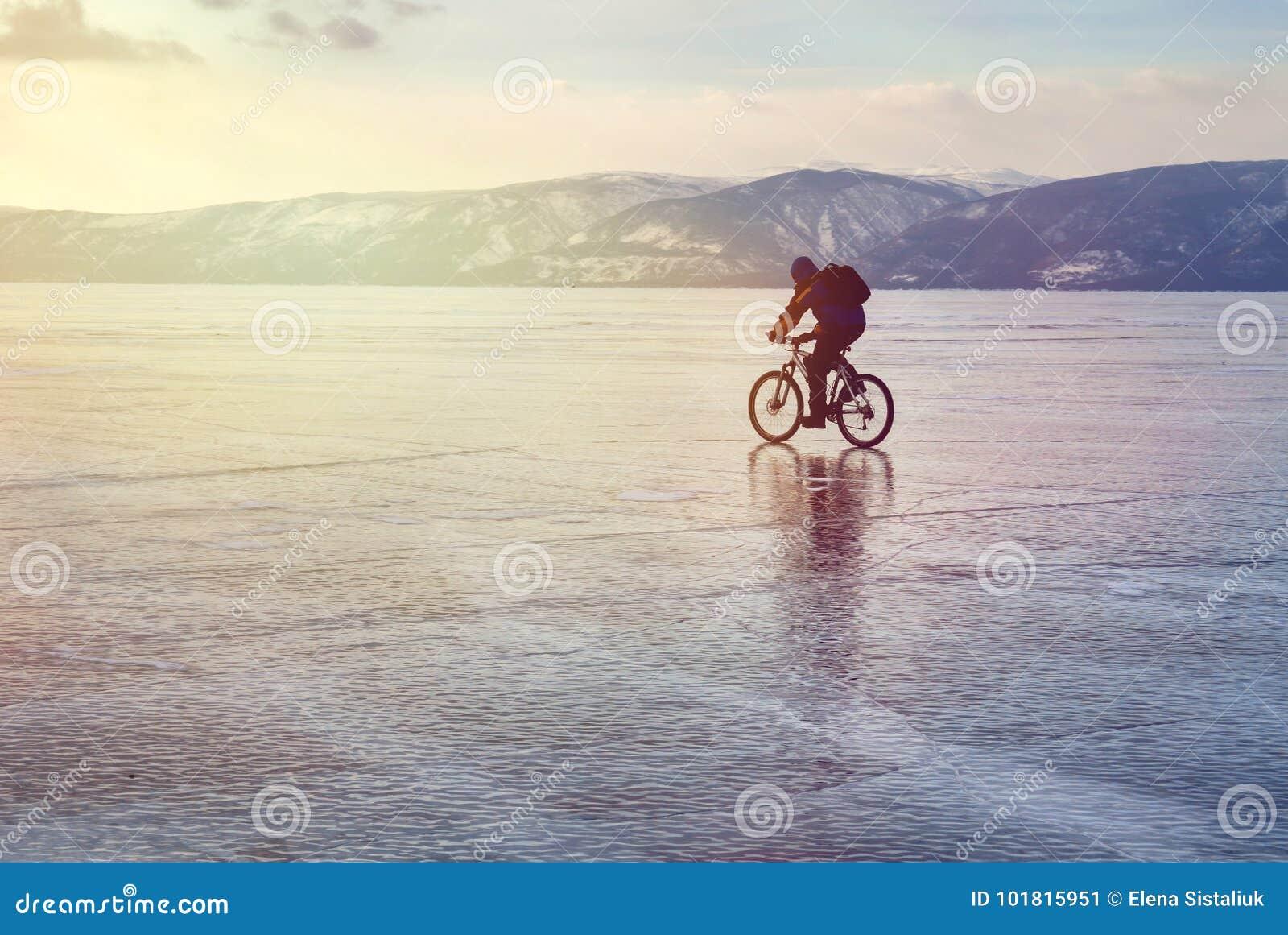 Congele o viajante do motociclista com as trouxas na bicicleta no gelo do Lago Baikal Na perspectiva do céu do por do sol, superf