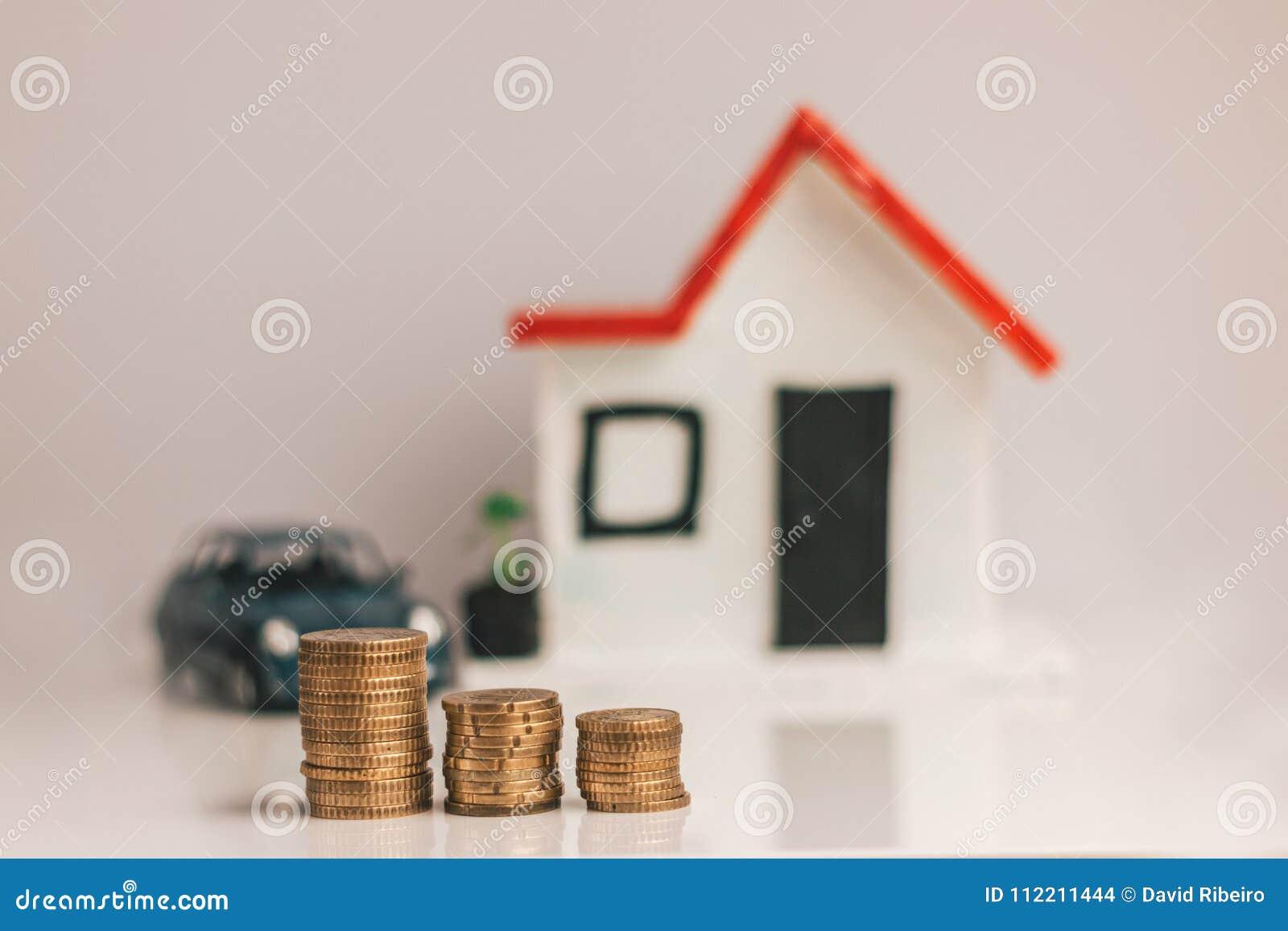 Coni la pila con una casa vaga e l automobile sui precedenti: bene immobile, proprietà, ipoteca, concetto finanziario di risparmi