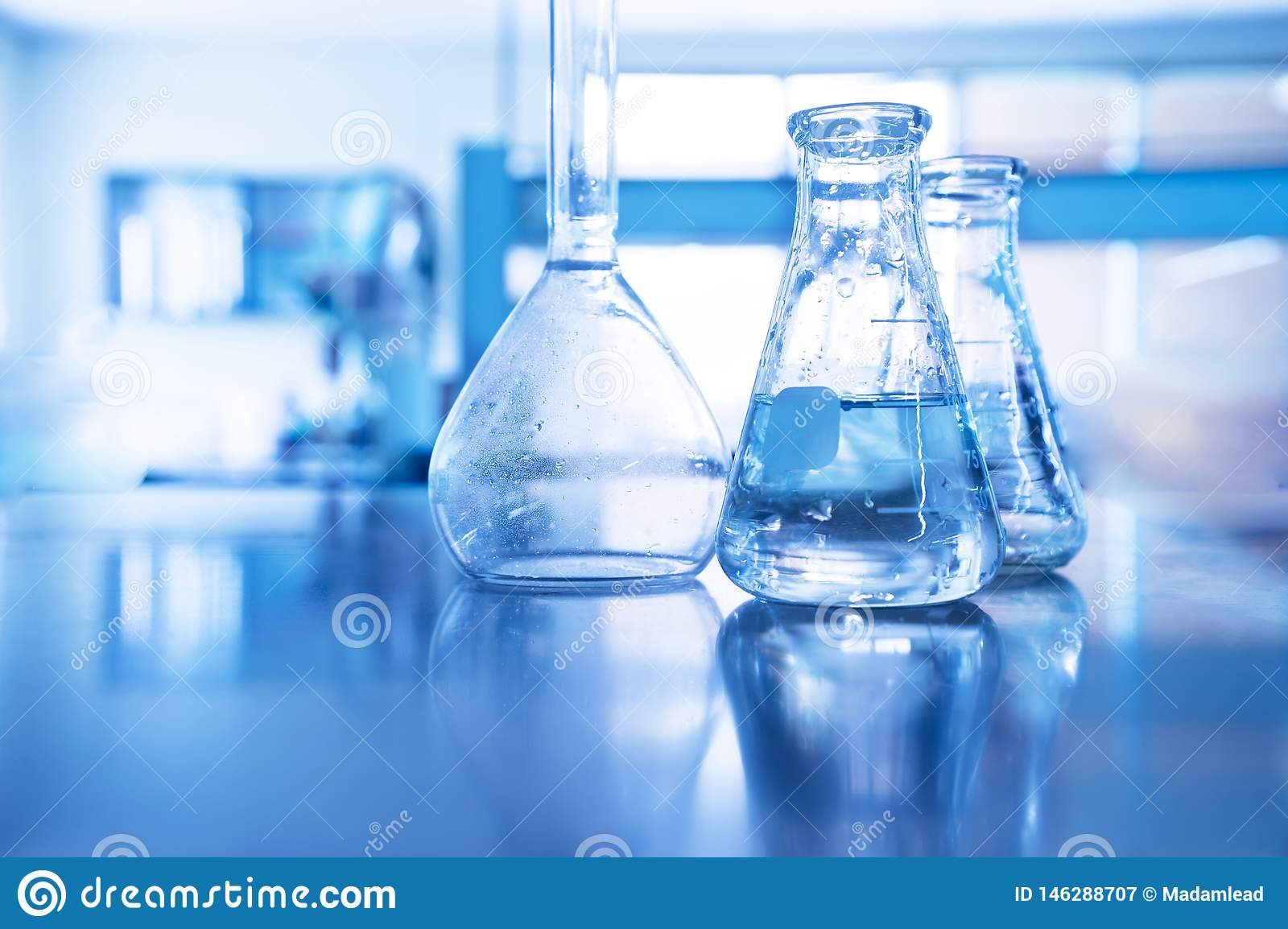 Conical and volumetric glass flask in science laboratory for blue education technology background