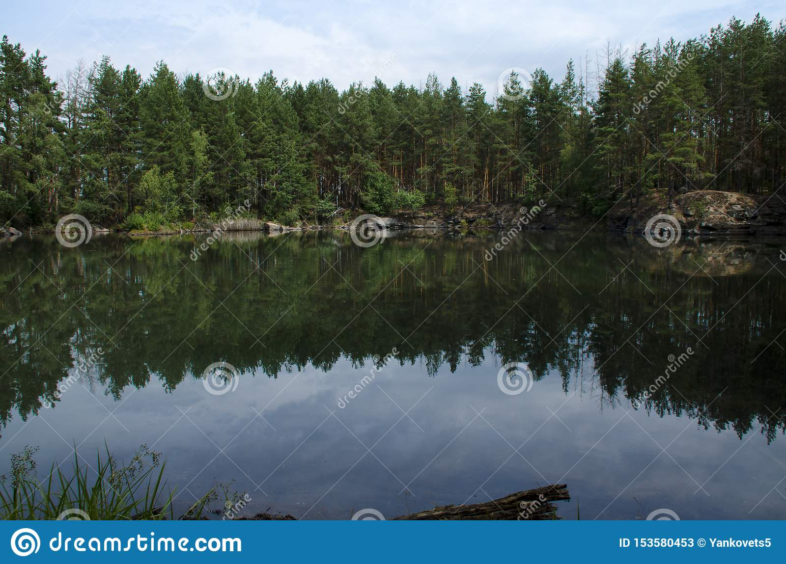 Coniferous forest is reflected in a lake with granite shores