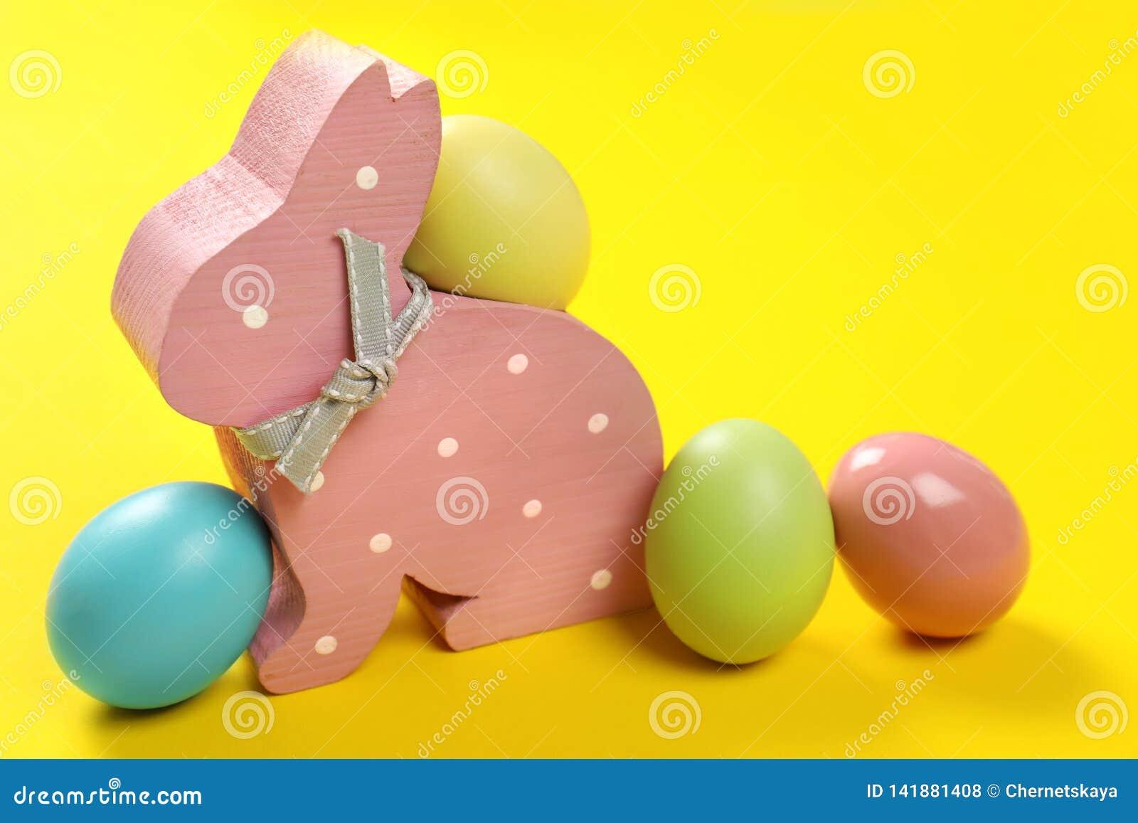 Coniglietto di pasqua di legno sveglio ed uova tinte
