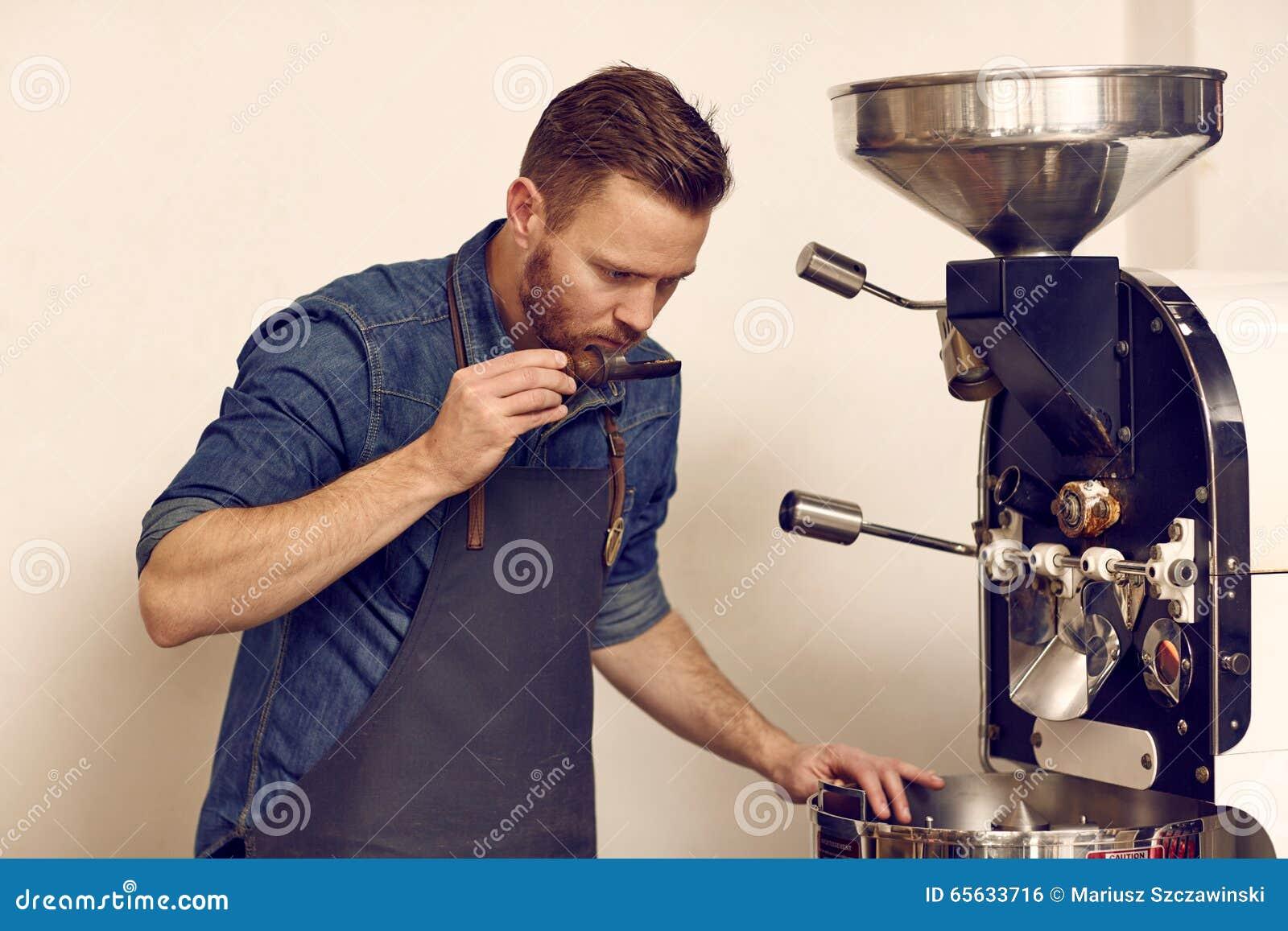 Connoiseur de café examinant les haricots fraîchement rôtis pour assurer le plein arome