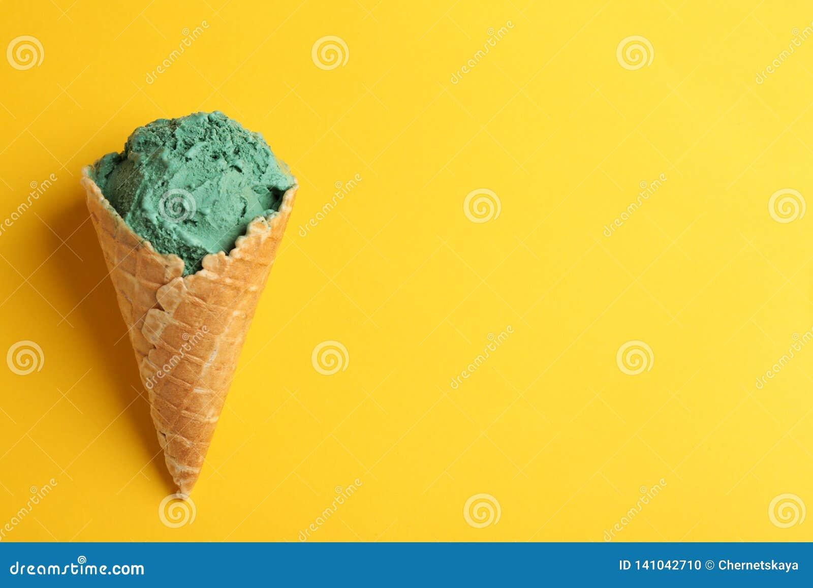 Cono de helado delicioso del spirulina en el fondo del color, visión superior