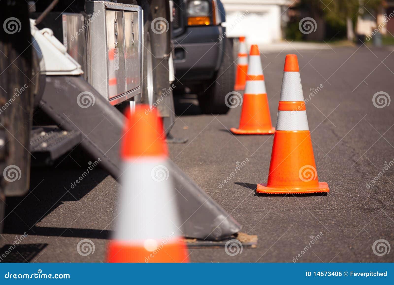 Conos anaranjados del peligro y carro utilitario en calle