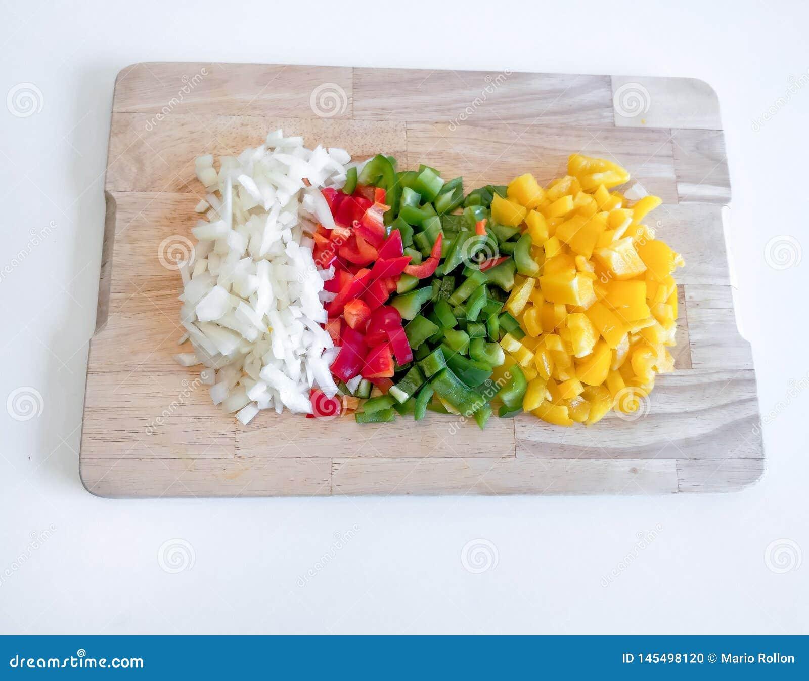 Conseil en bois avec jaune, vert, le rouge et les poivrons d oignon, sur le fond blanc