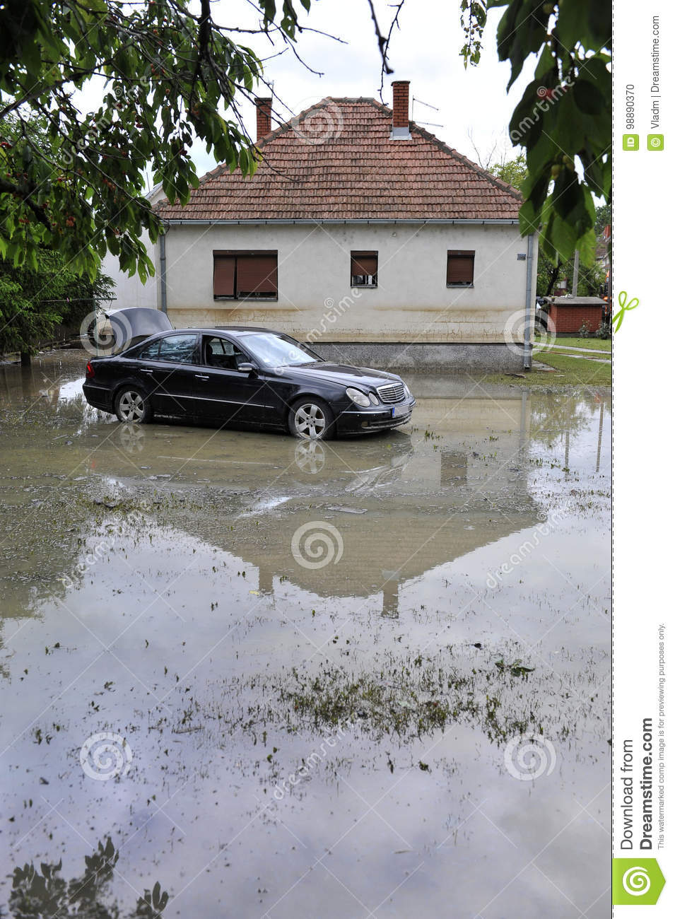 The consequences of flooding, car in front of flooded house.