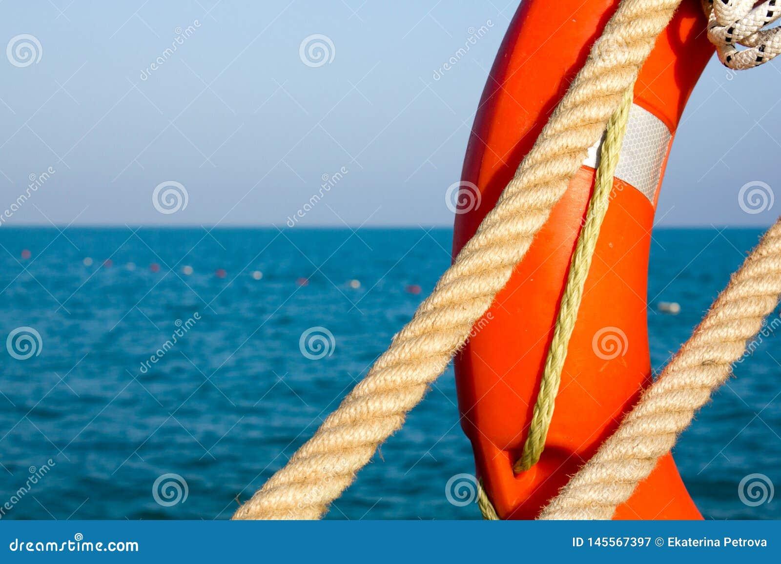 Conservante de vida anaranjado y cuerda marítima dos en el fondo del mar y del cielo azules Cierre para arriba Salvavidas en el f